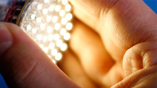 Hand baut LED-Strahler in Fassung ein